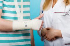 Man with broken hand visit doctor. - stock photo