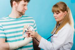 Female doctor checking heart beating. - stock photo