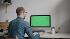 Caucasian worker typing on keyboard and looking at green screen - stock footage