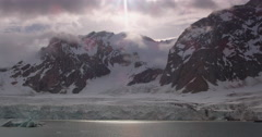 Sun shines through clouds onto icebergs in glacier fed bay Stock Footage