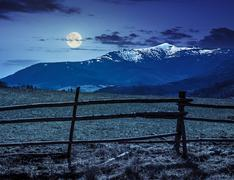 rural area with snowy mountain tops at night - stock photo