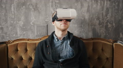 Man wearing virtual reality goggles. Studio shot, gray backgroun Stock Footage