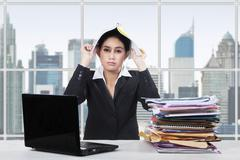 Bored worker puts paperwork on her head - stock photo