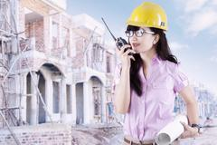 Female contractor with walkie-talkie - stock photo