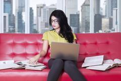 Female student sits on sofa while learning - stock photo