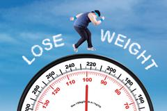 Man with text lose weight and scale - stock photo