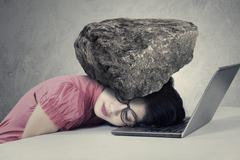 Stressed worker with a burden on her head - stock photo