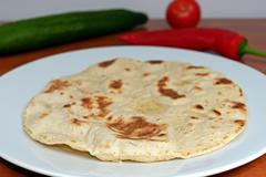 Homemade whole-wheat flour tortillas on a white plate on a wooden table in th - stock photo