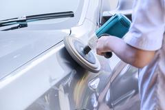 Worker waxing a car with auto polisher - stock photo