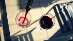 Pouring red wine into glass on terrace, top view, super slow motion 480fps Stock Footage