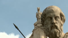 A view of the statues of Socrates in the foreground and Athena on the column - stock footage