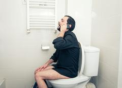 Man sitting in toilet and talking on phone Stock Photos