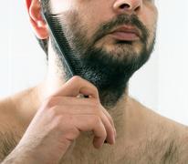 man combing beard hair closeup - stock photo