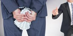 Composite image of rear view of businessman with handcuff and money Stock Photos