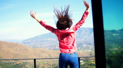 Excited woman jumping on terrace - stock footage