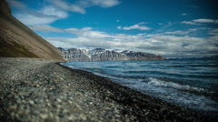 Timelapse of waves on arctic beach by mountains Stock Footage