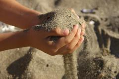 Young boy playing in the sand - stock photo