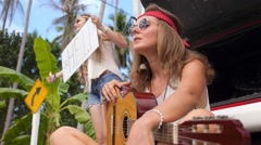 Freedom Hippie Girls with Guitar with Help Sign on Road Stock Footage