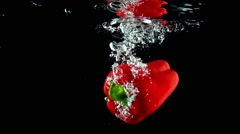 Stock Video Footage of Whole red ripe sweet pepper falls into water super slow motion video