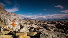 Timelapse of clouds over lichen covered rocks on arctic beach - stock footage
