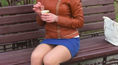 An attractive girl in a short skirt wand stirs the coffee in the Cup - stock footage