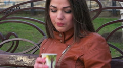 A lonely girl in a short skirt drinking coffee from a colorful Cup Stock Footage