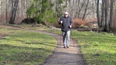 Tired hiker with walking sticks on path in the park Stock Footage