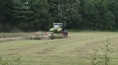 Tractor with a rotary rake on a field in Dutch coulissen landscape Stock Footage