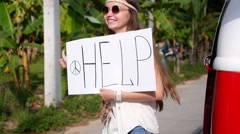 Hippie Hitchhiker Girl with Help Sign on Road Thumbs Her Way - stock footage