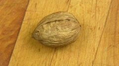 Walnut on the wooden desk - stock footage