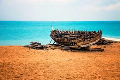 Wooden boat in decay by the sea, on the beach - stock photo