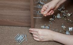 Furniture wooden assembly frame manually tightening screw using hex wrench. - stock photo