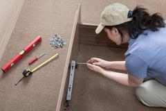 Woman housewife putting together assemble bed frame, using hand tools. Stock Photos