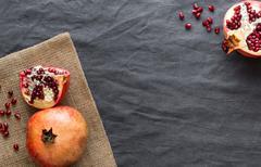 Pomegranate on dark textile background - stock photo