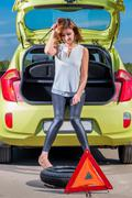 Young girl driver and a punctured wheel Stock Photos