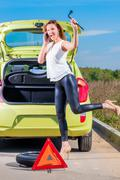 girl with phone and wrench is waiting roadside assistance - stock photo