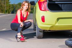 beautiful woman with with a wrench near the the green car - stock photo