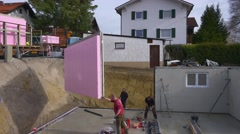 Prefabricated house, workers in setting up the basement walls Stock Footage