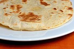Homemade whole-wheat flour tortillas on a white plate  on a wooden table - stock photo