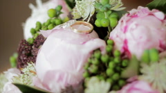 Wedding Rings Lie on a Bouquet of Peonies Stock Footage