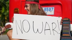 Hippie Girls with Anti-War Sign Playing Guitar on Road Stock Footage