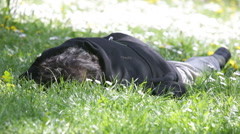 Homeless sleeping in the grass. Zooming out. - stock footage