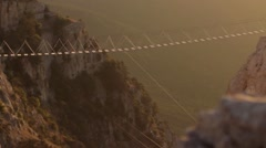 Rope ladder over the precipice and catholic cross on top of a mountain Stock Footage
