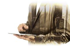 Double Exposure of Businessman use Computer Tablet with Phone Booth Stock Photos