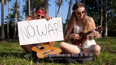 Joyful Hippie Girls Playing Guitar Outdoor with Antiwar Sign Stock Footage