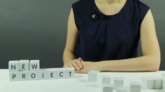"A Girl Builds the Phrase ""New Project"". Stock Footage"