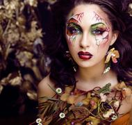 beauty woman with face art and jewelry from flowers orchids close up, creative - stock photo
