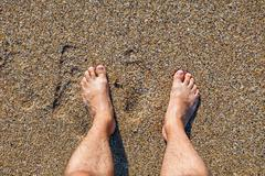 Male bare feet standing on the wet sandy beach - stock photo