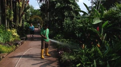 Man waters flowers in the National Orchid Gardens in Singapore, Singapore. Stock Footage