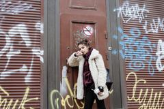 young pretty stylish teenage girl outside in city wall with graffity smoking - stock photo